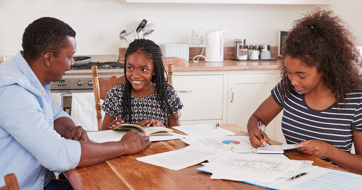 dad and daughters at kitchen table