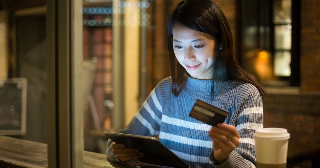 woman looking at credit card