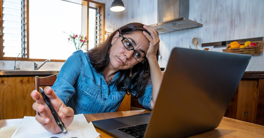upset woman looking at computer