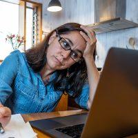 upset woman looking at computer