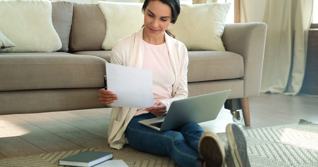 woman sitting on floor doing finances