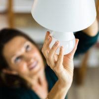 woman changing light bulb